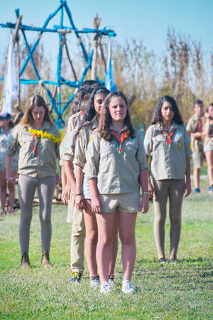 jewish group: TEL AVIV - MAY 9, 2015: Happy Israel Scouts marching in front of their families and other spectators during a yearly graduation passage ceremony in a Tel Aviv suburb