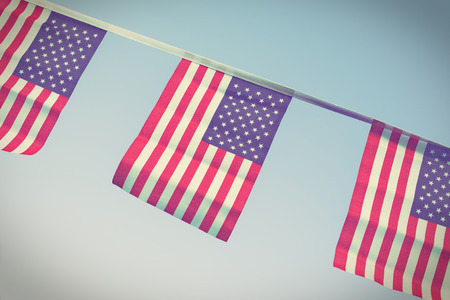independence: A chain  garland bunting of USA flags hanging proudly for July 4 Independence Day - vintage  retro  Instagram processed Stock Photo