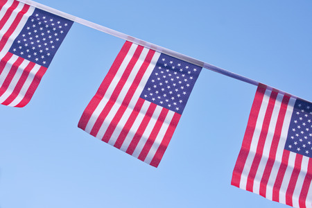 A chain / garland/ bunting of USA flags hanging proudly for July 4 Independence Day Standard-Bild