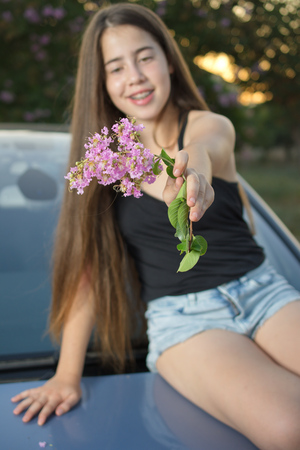 12 13: A 13 year old teenage girl with braces on her teeth sitting on a car enjoying pink flowers and the summer sunset (focus on the flowers) Stock Photo