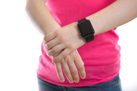 NEW YORK - JULY 9, 2015: Young woman in a pink shirt wearing an Apple Watch with a black Sports band