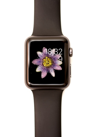 screenshot: NEW YORK - JULY 9, 2015: High resolution image of the Apple Watch screen: The MotionFace with time, date, and a blooming flower background.