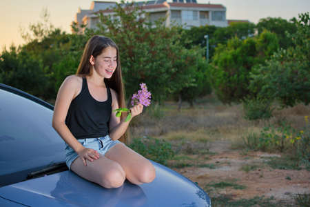 girl in shorts: A 13 year old teenage girl with braces on her teeth sitting on a car enjoying pink flowers and the summer sunset