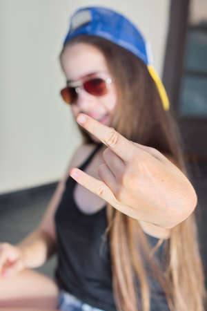 12 13: A cool 13 year old teenage girl in baseball cap and sunglasses making the Yo sign with her hand Stock Photo