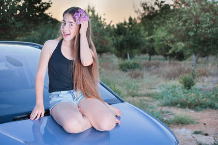 girl in shorts: A 13 year old teenage girl with braces on her teeth sitting on a car with flowers in her long hair enjoying the summer sunset Stock Photo