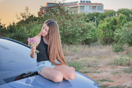 girl in shorts: A 13 year old teenage girl with braces on her teeth sitting on a car enjoying pink flowers and the Israeli summer sunset
