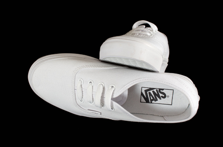 white person: NEW YORK - AUGUST 8, 2015: White Vans (Off the Wall) sneakers isolated on black