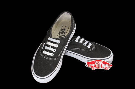 NEW YORK - AUGUST 8, 2015: Black and white Vans (Off the Wall) sneakers isolated on black
