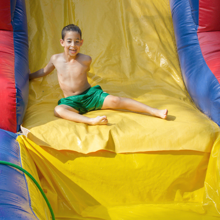 8 year old: 8 year old boy enjoying the summer while playing on a wet inflatable slide