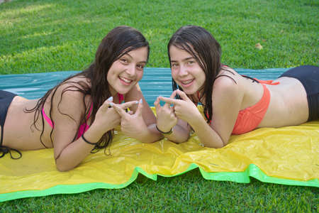 signify: Two pretty 14 year old best friends (teenage girls) enjoying the summer in bathing suites, making the infinity sign with their fingers to signify BFF