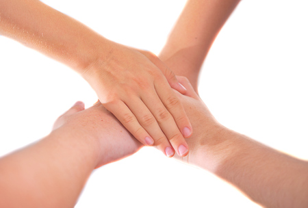 jewish group: Four girl friends holding hands in a pile of unity - isolated on white - showing teamwork and friendship Stock Photo