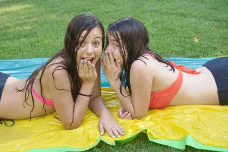 Zwei hübsche 14-jährige beste Freunde (Jugendlichen) genießen den Sommer in Baden-Suiten, auf einer Wasserrutsche liegen