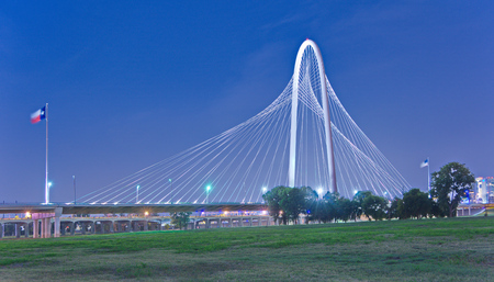 texas state flag: Margaret Hunt Hill Bridge and US flags at night in Dallas, Texas from Trinity Park