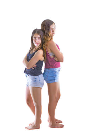 Two angry and upset 12 year old teenage girl best friends turning their back on each other - angry after a fight - isolated on white