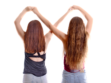 12 year old: Best Friends Forever - two 12 year old teenage girls  holding hands in an infinity forever sign to signify BFF - isolated on white Stock Photo