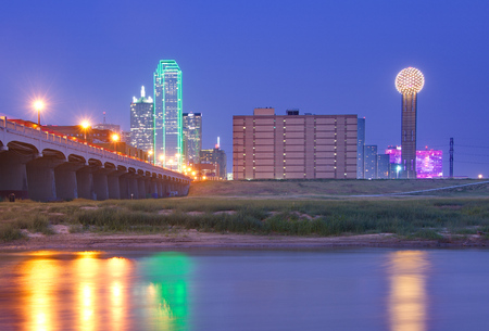 dallas: Downtown Dallas, Texas skyline at night including famous towers and  the Commerce Street Bridge, reflecting in the Trinity River