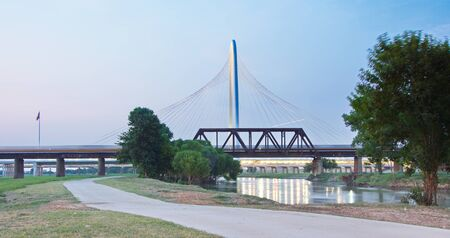 Margaret Hunt Hill Bridge and US flags at subset in Dallas, Texas from Trinity Park