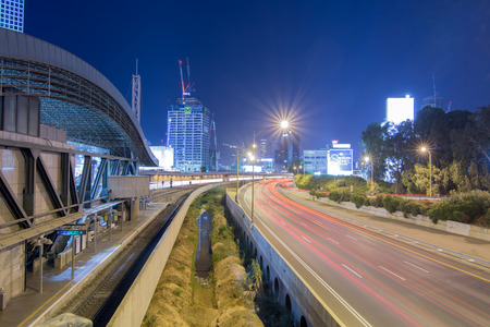 sky line: TEL AVIV - SEPT. 25, 2015: Tel Aviv at Night - Road 20 (Ayalon) and the Shalom Tain Station at night with car trails and the Tel Aviv modern sky line.