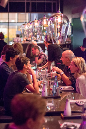 busy restaurant: TEL AVIV, SEPT 25, 2015: People having dinner in a modern and chik open kitchen restaurant in Israel.  Part of the hip Sarona district featuring restored Templer buildings. Editorial