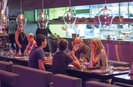 israel people: TEL AVIV, SEPT 25, 2015: People having dinner in a modern and chik open kitchen restaurant in Israel.  Part of the hip Sarona district featuring restored Templer buildings. Editorial