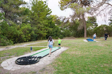 Sister and brother playing outdoor miniature golf in a Galilee forest in the north of Israel Stock Photo