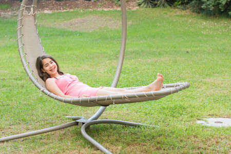 cute braces: A cute teenage girl, young woman, with braces on her teeth, enjoying the fresh mountain air on a modern outdoor hammock swing in the Galilee in the north of Israel