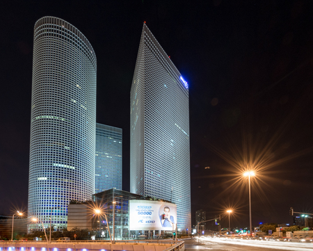 azrieli: TEL AVIV, ISRAEL - SEPT. 25, 2015: The thre Azrieli Center Towers and Mall in Downtown Tel Aviv at night, with car trails on the busy Kaplan Avenue