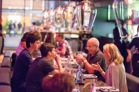 TEL AVIV, SEPT 25, 2015: People having dinner in a modern and chik open kitchen restaurant in Israel.  Part of the hip Sarona district featuring restored Templer buildings. Redactioneel