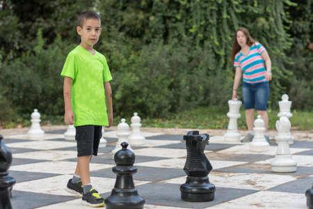 pensamiento estrategico: Hermano y hermana hermanos jugando una partida de ajedrez gigante al aire libre con piezas grandes en un parque verde al aire libre Foto de archivo