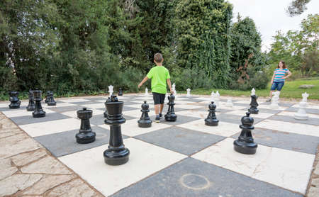 Brother and sister siblings playing a game of giant outdoor chess with big pieces in a green outdoor park Stock Photo