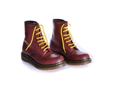 combat boots: A pair of 8 eyelet 8 inch classic unisex cherry red oxblood lace-up fashion combat boots with yellow laces