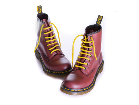 combat boots: NEW YORK - OCT. 28, 2015: A pair of Doc Martens 8 eyelet 8 inch classic unisex cherry red oxblood lace-up fashion combat boots with yellow laces