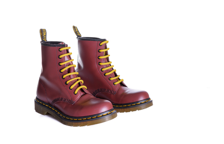 NEW YORK - OCT. 28, 2015: A pair of Doc Martens 8 eyelet 8 inch classic unisex cherry red oxblood lace-up fashion combat boots with yellow laces