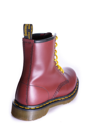 oxblood: NEW YORK - OCT. 28, 2015: A Doc Martens 8 eyelet 8 inch classic unisex cherry red oxblood lace-up fashion combat boot with yellow laces Stock Photo