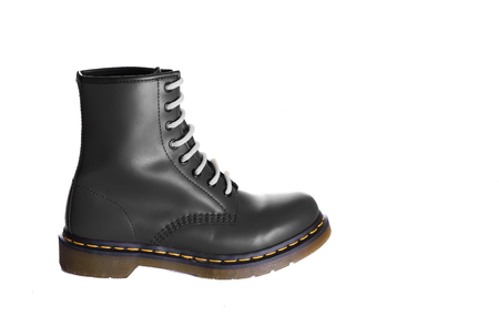 unisex: An 8 eyelet 8 inch classic unisex black lace-up fashion combat boot with white laces Stock Photo