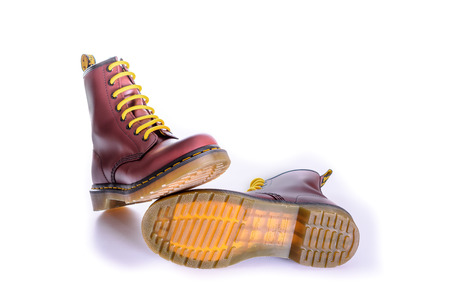 combat boots: NEW YORK - OCT. 28, 2015: A pair of Doc Martens 8 eyelet 8 inch classic unisex cherry red oxblood lace-up fashion combat boots with yellow laces with the sole showing