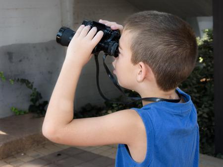high powered: 8 year old boy looking through a pair of high powered binoculars