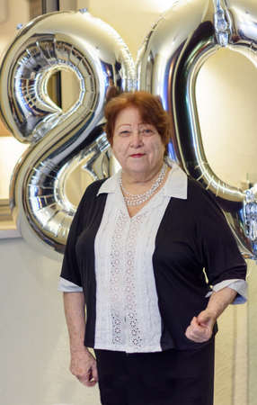 75 80: Young at heart elderly lady woman celebrating her 80th eightieth birthday with number shaped balloons Stock Photo