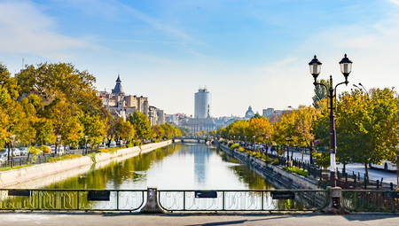 River Dambovita in Bucharest, Romania with the city skyline and colorful trees in foliage Stok Fotoğraf