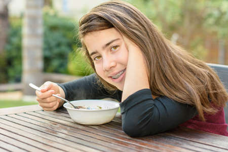 12 13: A teenage girl with braces on her teeth enjoying hot chicken soup (a.k.a. the Jewish Penicillin) in a cold autumn day Stock Photo