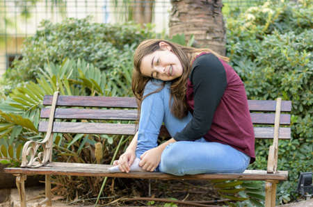 12 13: Teenage girl with orthodontic braces on her teeth enjoying the cool autumn weather while sitting on a wooden bench Stock Photo