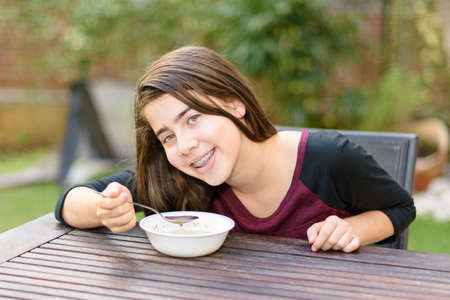 jewish penicillin: A teenage girl with braces on her teeth enjoying hot chicken soup (a.k.a. the Jewish Penicillin) in a cold autumn day Stock Photo