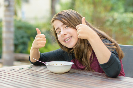 A teenage girl with braces on her teeth giving a thumbs up to hot chicken soup (a.k.a. the Jewish Penicillin) in a cold autumn day Stock Photo