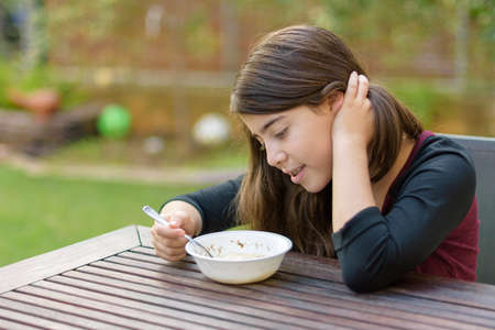 A teenage girl with braces on her teeth enjoying hot chicken soup (a.k.a. the Jewish Penicillin) in a cold autumn day Stock Photo