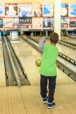 An 8 year old boy enjoying a game of bowling in a retro style bowling alley near Tel Aviv, Israel featuring old-time bowling adds.