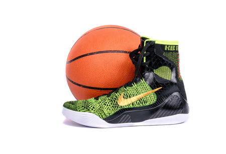nike: NEW YORK - DEC. 15, 2015: An ultra modern Nike Kobe IX Elite Victory high-top green and black flyknit basketball shoe sneaker with a basketball, isolated on white