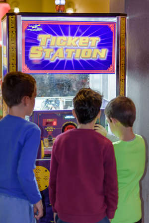 arcade games: KFAR SABA, ISRAEL - DEC. 12, 2015: 8 year old kids having fun at the arcade with video games, lottery machines, tickets, and prizes.