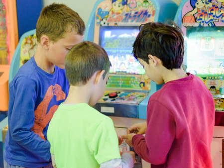 8 year old: KFAR SABA, ISRAEL - DEC. 12, 2015: 8 year old kids having fun at the arcade with video games, lottery machines, tickets, and prizes.