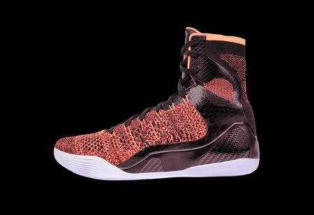 ultra modern: Ultra modern high-top orange and black basketball shoe sneaker, isolated on black Stock Photo