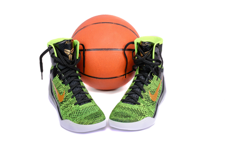 ultra modern: NEW YORK - DEC. 15, 2015: A pair of ultra modern Nike Kobe IX Elite Victory high-top green and black flyknit basketball shoes sneakers with a basketball, isolated on white